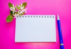 Bloc-notes en spirale vide, fleurs et stylo bleu Photographie stock libre de droits