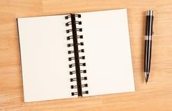 Bloc - notes et crayon lecteur spiralés blanc sur le bois Photo stock