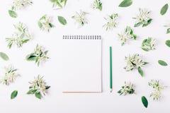 Bloc-notes et crayon parmi les fleurs vertes Image libre de droits