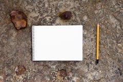 bloc-notes et crayon sur le plancher en béton Photo stock