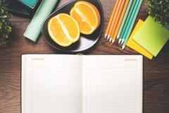 Bloc-notes et fruit vides de livre à couverture dure sur le bureau Photos libres de droits
