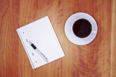 Bloc-notes et une tasse de café sur la table en bois de l'abov Images stock