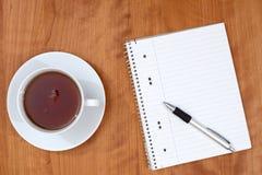 Bloc-notes et une tasse de thé sur la table en bois de l'abov Images libres de droits