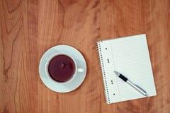 Bloc-notes et une tasse de thé sur la table en bois de l'abov Photo libre de droits