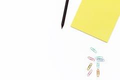 Bloc-notes jaune, crayon noir, et trombones colorés sur un fond blanc concept minimal d'affaires Loi plate Photos libres de droits