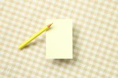 Bloc-notes jaune de note et crayon coloré jaune sur le fond beige de tissu photographie stock