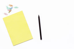 Bloc-notes jaune, un crayon et un trombone Concept minimal d'affaires de lieu de travail dans le bureau Images stock