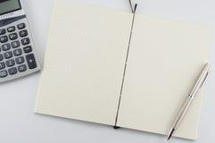 Bloc-notes ouvert avec le stylo et la calculatrice Image libre de droits