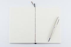 Bloc-notes ouvert avec le stylo sur le fond blanc Photos stock
