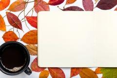 Bloc-notes ouvert avec les feuilles d'automne et la tasse de café en baisse Images libres de droits