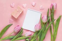 Bloc-notes ouvert de blanc avec des tulipes et des coeurs sur un fond rose Photos libres de droits