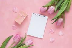Bloc-notes ouvert de blanc avec les tulipes, le boîte-cadeau et les coeurs sur un Ba rose Photos stock