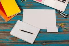 Bloc-notes, page vide, journaux intimes, stylos, crayons de couleur, ordinateur portable et goupilles de papier Photographie stock