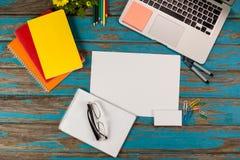 Bloc-notes, page vide, lunettes, journaux intimes, stylos, crayons de couleur, ordinateur portable et goupilles de papier Photos libres de droits