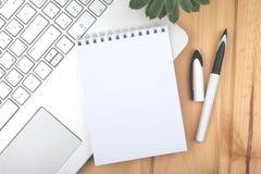 Bloc-notes propre sur l'ordinateur portable près du stylo élégant image stock
