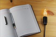 Bloc-notes, stylo, calculatrice, et une lampe brûlante sur une surface en bois Images stock
