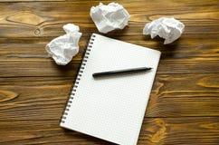 Bloc-notes, stylo et feuilles de papier chiffonnées sur la table en bois Manque d'idée Photographie stock libre de droits