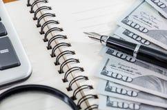Bloc-notes, stylo, loupe, calculatrice et dollars images libres de droits