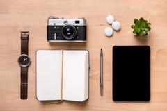 Bloc-notes, stylo, montre, appareil-photo de vintage, comprimé et fleur vides ouverts Photographie stock libre de droits