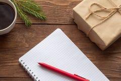 Bloc-notes, stylo rouge, tasse de café et cadeau sur la table en bois photos stock