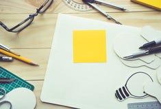 Bloc-notes sur la table de travail avec des éléments des outils, équipement Photographie stock