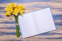 Bloc-notes sur un conseil en bois Fleurs jaunes de jonquilles sur une table en bois Photo libre de droits