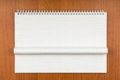 Bloc-notes sur une spirale avec une feuille courbée se trouvant sur une table Photographie stock