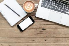 Bloc-notes, téléphone portable et ordinateur portable sur la table en bois photo libre de droits