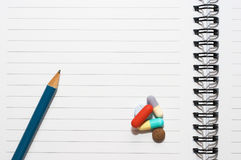 Bloc-notes, un crayon, pillules Photo stock