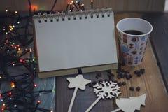 Bloc-notes, un verre avec la copie de bonhomme de neige et décorations sur un tablen Photographie stock
