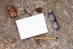 bloc-notes, verres et crayon sur le plancher en béton Image stock