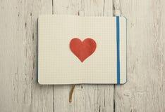 Bloc-notes vide avec le coeur rouge sur le bois Images stock