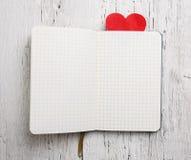 Bloc-notes vide avec le coeur rouge sur le bois Image libre de droits