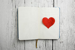 Bloc-notes vide avec le coeur rouge sur le bois Image stock