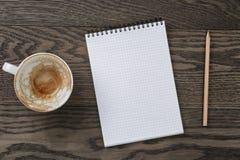 Bloc-notes vide avec le crayon et la tasse de café vide sur la table en bois Photos stock