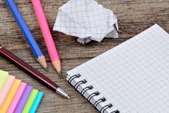Bloc-notes vide avec les notes colorées d'ANC de crayons sur la table Photo libre de droits