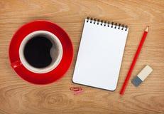 Bloc-notes vide avec les fournitures de bureau et le café Photos stock