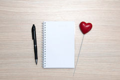 Bloc-notes vide, crayon et coeur rouge sur la table en bois Images stock