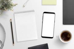 Bloc-notes vide et maquette futée moderne de téléphone sur le bureau blanc entouré avec des fournitures de bureau Photo stock