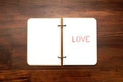 Bloc-notes vide ouvert avec le mot tiré AMOUR sur la table en bois Photographie stock libre de droits