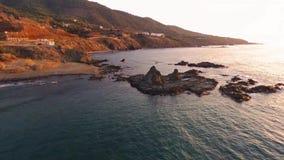 Bloccaggio del fuco di bella spiaggia rocciosa al tramonto in Pomos, Cipro stock footage