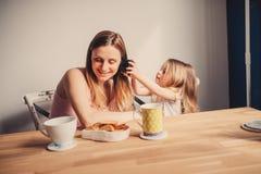 Bloccaggio di stile di vita della madre felice e della neonata che mangiano prima colazione a casa immagine stock