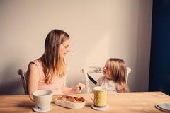 Bloccaggio di stile di vita della madre felice e della neonata incinte che mangiano prima colazione a casa immagine stock