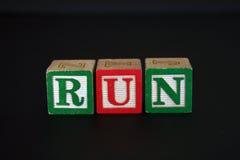 Blocchetti del giocattolo che ortografano l'ESECUZIONE Immagine Stock