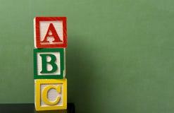Blocchetti di ABC davanti alla lavagna Immagini Stock