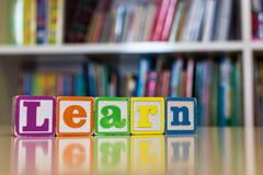 Blocchetti di alfabeto che compitano la parola per imparare davanti ad uno scaffale per libri fotografie stock