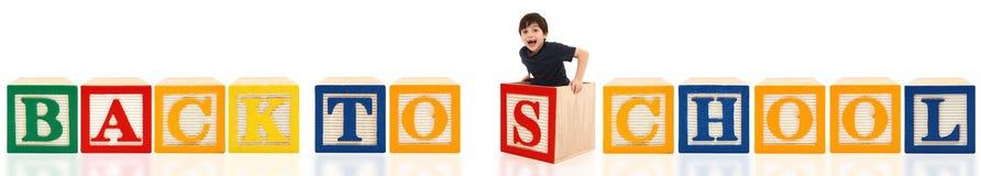Blocchetti di alfabeto di nuovo al banco con il ragazzo Immagine Stock