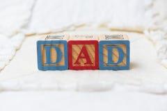 Blocchetti di legno di alfabeto sul papà di ortografia della trapunta Fotografia Stock Libera da Diritti