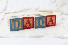 Blocchetti di legno di alfabeto sulla trapunta Dada d'ortografia Immagine Stock Libera da Diritti