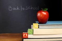 Blocchetti e mela di ABC contro il bordo nero Fotografia Stock